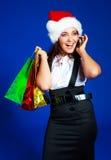 Ragazza con i sacchetti che comunica sul telefono Fotografie Stock