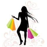 Ragazza con i sacchetti della spesa su fondo floreale Fotografie Stock