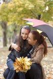 Ragazza con i suoi la madre e fogli di colore giallo Fotografia Stock