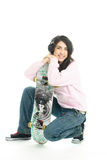 Ragazza con i trasduttori auricolari e un boeard del pattino Fotografia Stock Libera da Diritti