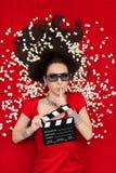Ragazza con i vetri del cinema 3D, il popcorn e direttore Clapboard Asking per silenzio Fotografia Stock