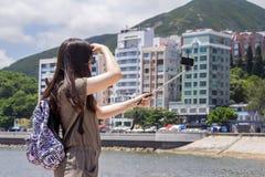 Ragazza con il bastone del selfie che prende immagine Immagine Stock Libera da Diritti