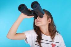 Ragazza con il binocolo che cerca lo spazio della copia Fotografie Stock