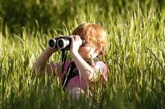 Ragazza con il binocolo dal lato Fotografie Stock