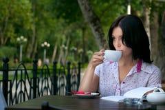 Ragazza con il blocchetto per appunti in caffè Fotografia Stock Libera da Diritti
