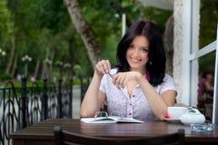 Ragazza con il blocchetto per appunti in caffè Fotografia Stock