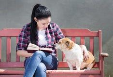 Ragazza con il cane che legge un libro Fotografia Stock