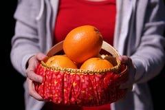 Ragazza con il canestro arancio per i regali cinesi del nuovo anno Fotografie Stock