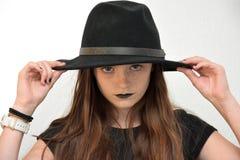 Ragazza con il cappello del ` s degli uomini di colore e le labbra nere fotografie stock