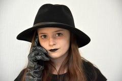 Ragazza con il cappello del ` s degli uomini di colore ed i guanti argentei fotografia stock libera da diritti