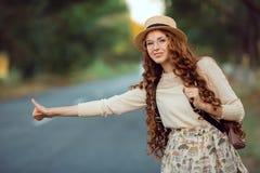 Ragazza con il cappello e lo zaino che fa auto-stop sulla strada Fotografie Stock