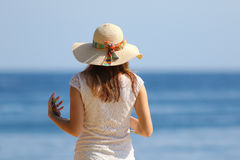 Ragazza con il cappello ed il telefono cellulare sulla spiaggia Immagini Stock
