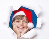Ragazza con il cappuccio di Santa che guarda da un foro in una carta Fotografie Stock