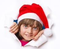 Ragazza con il cappuccio di Santa che guarda da un foro in una carta Immagini Stock