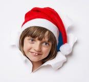 Ragazza con il cappuccio di Santa che guarda da un foro in una carta Immagini Stock Libere da Diritti