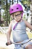 Ragazza con il casco rosa, i vetri neri e la bicicletta Immagini Stock