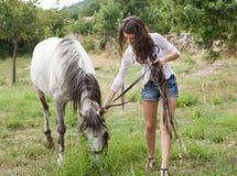 Ragazza con il cavallo dell'azienda agricola Fotografia Stock