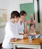 Ragazza con il compagno di classe allo scrittorio nel laboratorio di scienza Immagini Stock Libere da Diritti