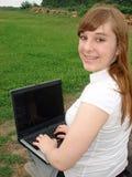 Ragazza con il computer portatile Fotografie Stock Libere da Diritti