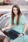 Ragazza con il computer portatile all'aperto Fotografie Stock Libere da Diritti