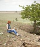 Ragazza con il computer portatile alla roccia vicino al lago ed all'albero. Fotografia Stock