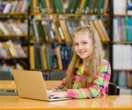 Ragazza con il computer portatile in biblioteca Fotografia Stock
