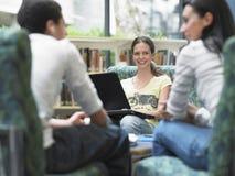 Ragazza con il computer portatile che esamina gli amici in biblioteca Immagini Stock