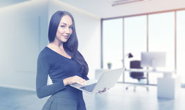 Ragazza con il computer portatile che posa nel suo boss& x27; ufficio di s Immagini Stock