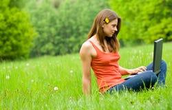 Ragazza con il computer portatile che si distende sull'erba, 'comm libero Fotografia Stock