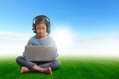 Ragazza con il computer portatile che si siede sul cielo blu dell'erba verde Fotografia Stock