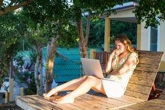 Ragazza con il computer portatile che si siede sul recliner nell'aria aperta vicino alla casa funzionamento Fotografie Stock