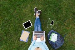 Ragazza con il computer portatile che si siede sull'erba verde Fotografia Stock Libera da Diritti