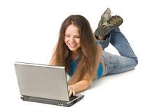 Ragazza con il computer portatile che si trova sul pavimento Fotografia Stock