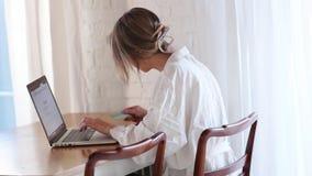 Ragazza con il computer portatile che tiene una carta di credito archivi video