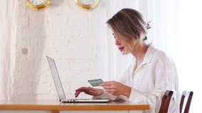 Ragazza con il computer portatile che tiene una carta di credito video d archivio