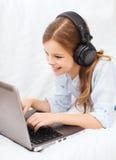 Ragazza con il computer portatile e le cuffie a casa Fotografie Stock