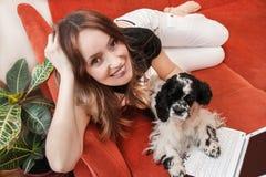 Ragazza con il computer portatile ed il cane Fotografia Stock