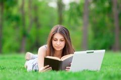 Ragazza con il computer portatile ed il libro Immagini Stock Libere da Diritti