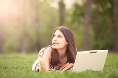 Ragazza con il computer portatile ed il libro Immagini Stock