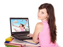 Ragazza con il computer portatile ed il libro aperti. Immagini Stock Libere da Diritti