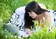 ragazza con il computer portatile nel parco Immagine Stock