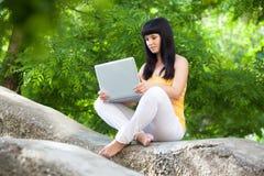 ragazza con il computer portatile nel parco Fotografie Stock