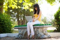 ragazza con il computer portatile nel parco Fotografia Stock Libera da Diritti
