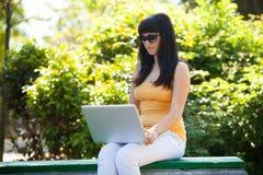 ragazza con il computer portatile nel parco Fotografie Stock Libere da Diritti