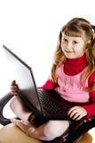 Ragazza con il computer portatile in presidenza Fotografia Stock