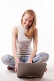 Ragazza con il computer portatile su bianco Fotografia Stock