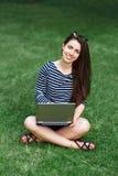 Ragazza con il computer portatile su erba Fotografie Stock