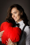Ragazza con il cuscino in forma di cuore Fotografia Stock
