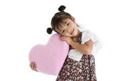 Ragazza con il cuscino a forma di del cuore Fotografia Stock
