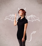 Ragazza con il disegno dei corni e delle ali del diavolo Immagini Stock